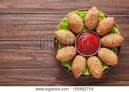 Kibbeh homemade beef, lamb, goat or camel meat stuffed bulgur kofta spicy meatball fried croquettes on green salad food on rustic wooden table background