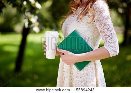 Girl in elegant lace dress holding a book and a disposable coffee cup