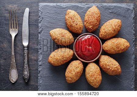 Kibbeh traditional Levantine middle eastern beef, lamb, goat or camel meat stuffed bulgur kofta spicy meatball fried croquettes dinner food on dark table background