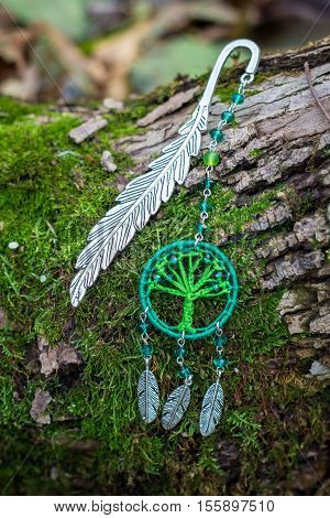 metal bookmark with dream catcher handmade on the bark and mos of a tree
