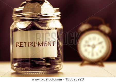 Close up Coins in glass jar with alarm clock for time to money saving for retirement concept vintage color tone