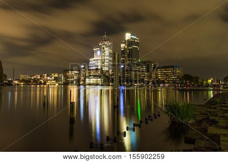 The Amsterdam city center by night featuring a modest skyline composed of the Rembrandt Mondriaan and Breitner towers on the bank of the Amstel river.