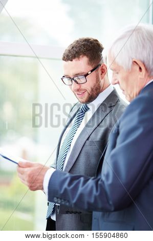 Business partners examining a document together in office building