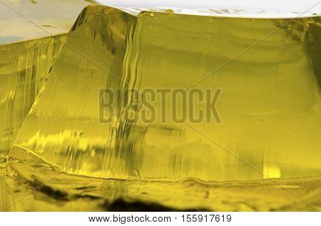 Closeup jelly shot. Abstract yellow gelatin dessert.