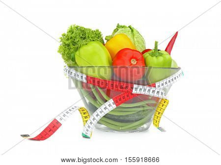 Fresh salad and measuring tape on white background