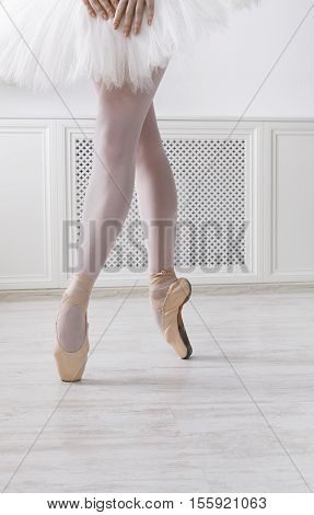 Closeup of young ballerina legs, stands in pointe shoes at white wooden floor background, with copy space. Ballet practice. Beautiful slim graceful feet of ballet dancer. Vertical