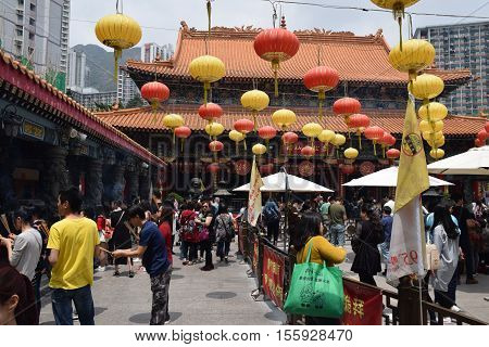 HONG KONG, CHINA - APRIL 03, 2016 - Unidentified crowd of chinese people and lanterns inside Wong Tai Sin temple, Hong Kong