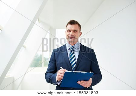 serious mid adult businessman holding folder with papers
