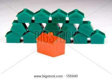 Red Plastic House In Front Of A Neat Stack Of Green Ones