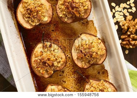 Sweet baked pear halves topped with a crisp crust of oatmeal sugar and walnut sprinkled with cinnamon photographed overhead with natural light (Selective Focus Focus on the top of the crusts on the pears)