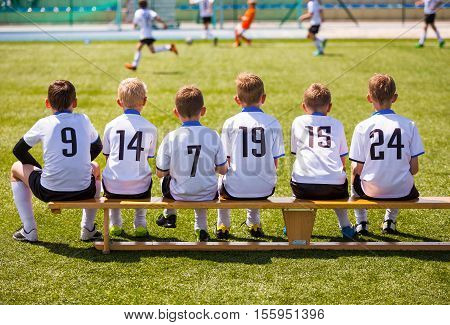 Young Football Players. Young Soccer Team Sitting on Wooden Bench. Soccer Match For Children. Young Boys Playing Tournament Soccer Match. Youth Soccer Club