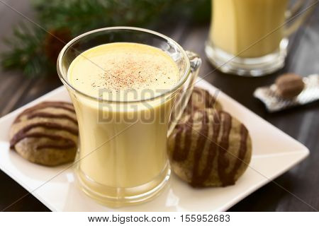 Eggnog with freshly grated nutmeg on the top gingerbread cookies on the side photographed with natural light (Selective Focus Focus one third onto the top of the eggnog)
