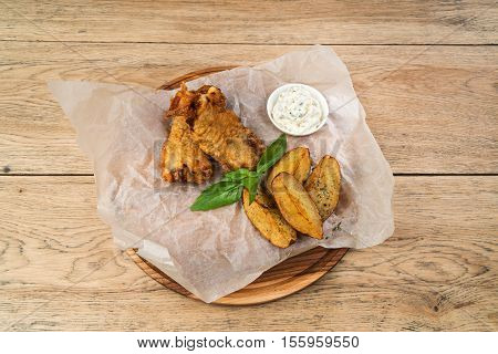 Fried fish in batter with potatoes and tartar sauce served on a wooden tray on paper