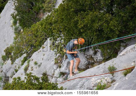 An unidentified man climbing down in a canyon of Verdon in Alpes-De-Haute-Provence France