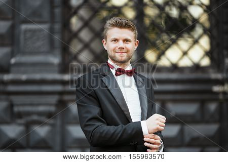Wedding photo shooting. Bridegroom standing outdoor. Man wearing white shirt, black jacket and bow-knot. Waist up, looking at camera