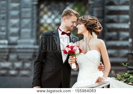 Wedding photo shooting. Bride and bridegroom standing with bouquet. Looking at each other. Woman wearing white dress and veil and man wearing suit. Outdoor, waist up, profile
