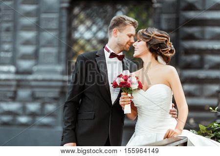 Wedding photo shooting. Bride and bridegroom standing with bouquet. Looking at each other and smiling. Woman wearing white dress and veil and man wearing suit. Outdoor, waist up, profile