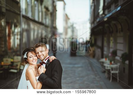 Wedding photo shooting. Bride and bridegroom at street. Embracing with closed eyes and smiling. Outdoor, waist up