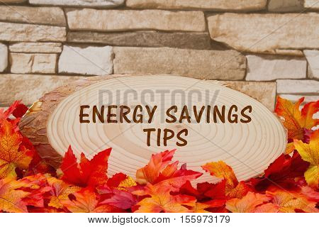 Energy savings tips message Some fall leaves a pumpkin and wood plaque on weathered brick with text Energy Savings Tips