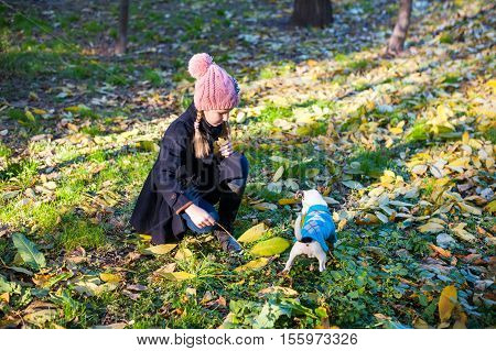 A little blond play girl with her pet dog jack russel terrieroutdooors in park
