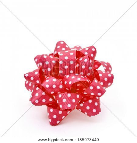 a gift puff bow made with red ribbon patterned with white dots, on a white background