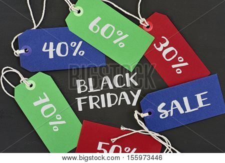 text black friday written in white and paper labels of different colors with different percentages  of discount, against a dark gray background