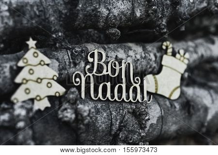 the text bon nadal, merry christmas in catalan language, a christmas tree and a christmas stocking, on a pile of logs