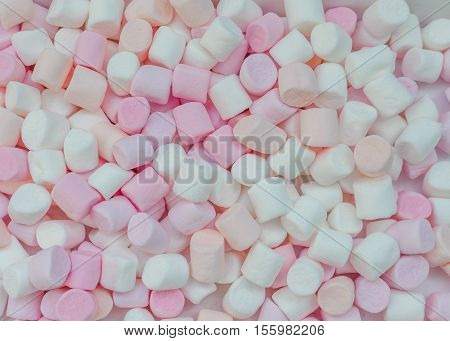 Colorful mini marshmallows background close-up texture. A pile of different mini white pink and orange puffy marshmallows. Marshmallow concept. Wallpaper for desktop. Top view.