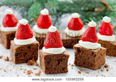 Santa Hat Brownie Bites with strawberries and whipped cream or cheese frosting - creative Christmas dessert idea for festive party