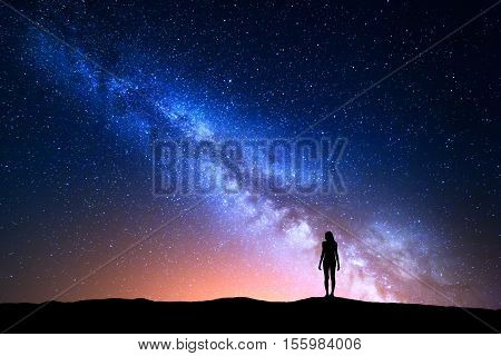 Beautiful Milky Way with standing woman. Colorful landscape with night sky with stars and silhouette of a girl on hill on the background of beautiful galaxy. Blue milky way with yellow light. Travel