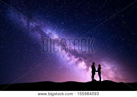 Milky Way with silhouette of people. Landscape with night sky with stars and standing man and woman holding hands on the mountain. Hugging couple against purple milky way. Beautiful galaxy. Universe