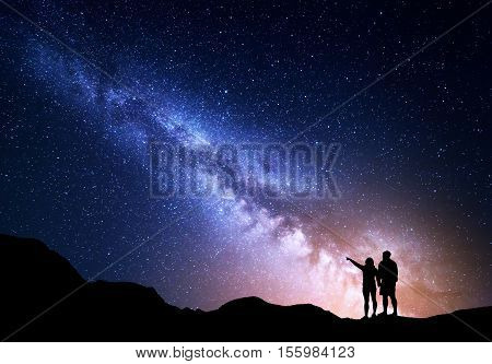 Milky Way with people on the mountain. Landscape with night sky with stars and silhouette of standing happy man and woman who pointing finger in starry sky. Milky way with travelers. Beautiful galaxy