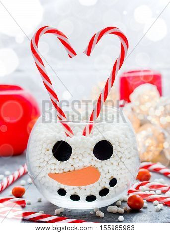 Snowman face glass bowl kid diy for Christmas sweet treats for children Happy New Year and Merry Christmas concept background