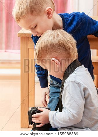 Technology and childhood. Discovering and fun. Children play and take photo in home. Boys hold camera look at screen.