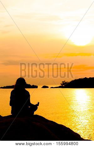 Silhouette, Woman Meditating In Yoga Pose Or Lotus Position By The Sea At Sunset. Rear View. Nature