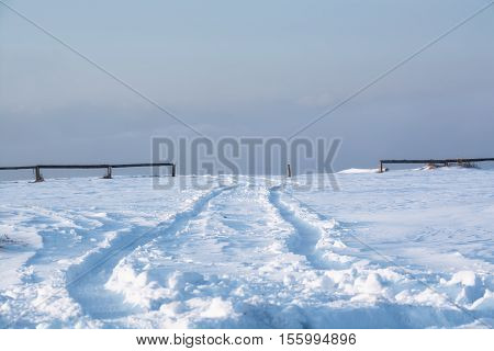 Trail of wheels on the snow surface. Track which go to the passageway between wooden railings.
