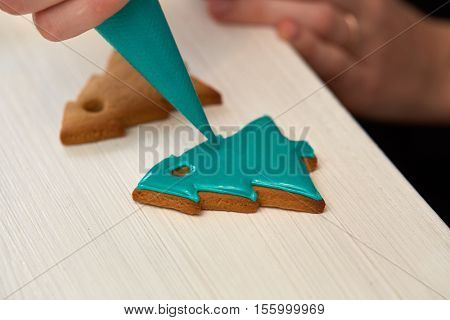 Christmas Treats. Handmade cookies, confection standing on the table. Female hands decorating gingerbread with icing sugar using a pipping bag. Baking holiday cookies. Christmas and New Year.