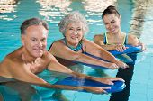 Happy senior couple taking swimming lessons from young trainer. Smiling old woman and mature man doi poster