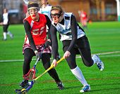 Girls Lacrosse scooping the ball