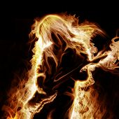 stock photo of ember  - Musician with an electronic guitar enveloped in flames on a black background - JPG
