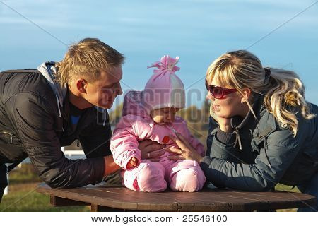Caucasian Young Family With Baby On Wood Table,
