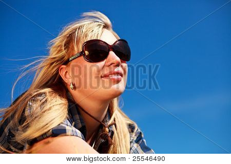 Blonde Girl In Checkered Skirt And Sunglasses Portrait On Blue Sky Background.