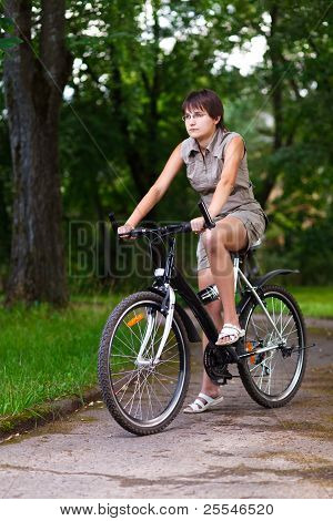 Girl On Bicycle In A Park.