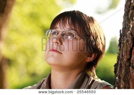 Portrait Of Dreamy Girl In Glasses Near A Tree.