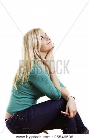 Blond Young Woman In Jeans And Sweater Dreaming. Isolated On White Background.