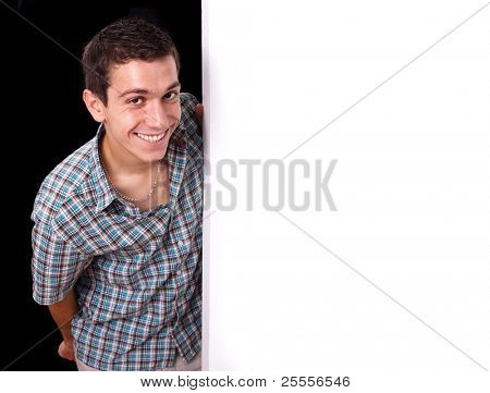 Portrait of a  young man peeking behind empty white wall