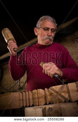 Old woodcarver work in the workshop 7