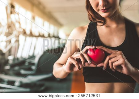 poster of Happy Sport Woman Holding Red Heart In Fitness Gym Club. Medical Cadio Heart Strength Training Lifes