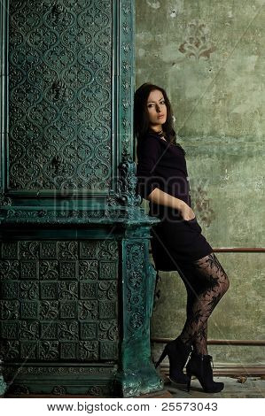 Beautiful girl near a fireplace with patterns in an old house