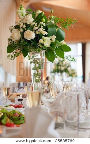 Table setting for a wedding or dinner event, with flowers in vase of glass